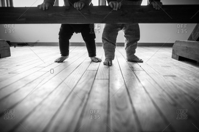 Two babies standing holding wooden rail