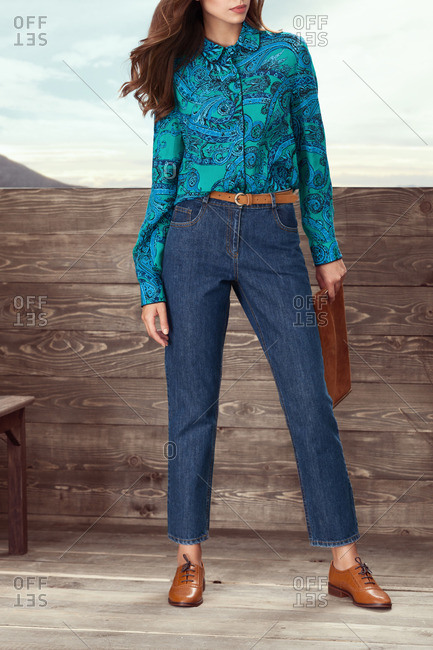 Woman modeling denim jeans and button front shirt