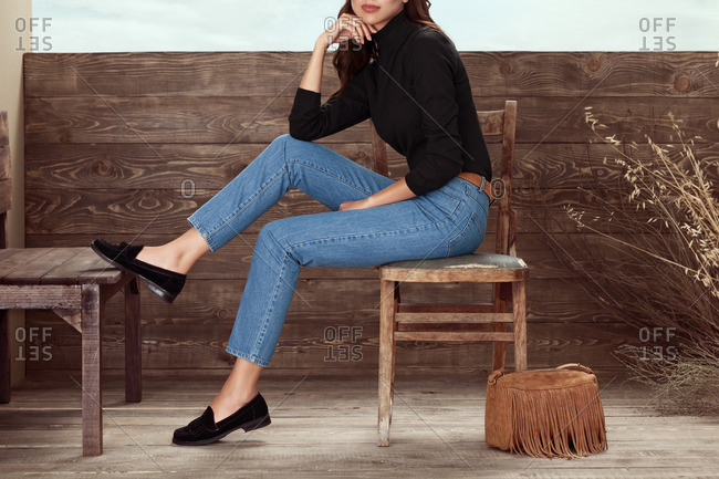 Woman in jeans sits on chair with suede fringed bag