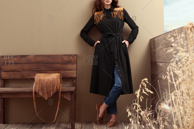 Woman models a suede-fringed black trench coat with fringe bag on bench