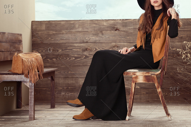 Woman in black dress with fringed suede vest