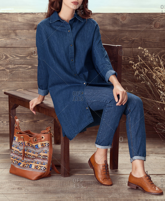 Woman in long denim tunic and jeans with patterned handbag