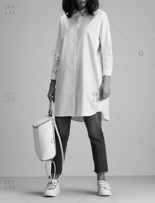 Woman in an oversized shirt holding a white leather backpack