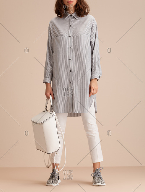 Woman in a pinstripe shirt holding a white leather backpack