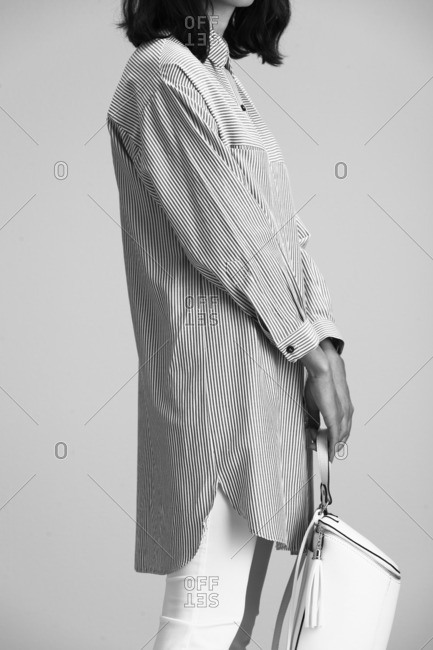 Woman in a button-down pinstripe shirt with a backpack