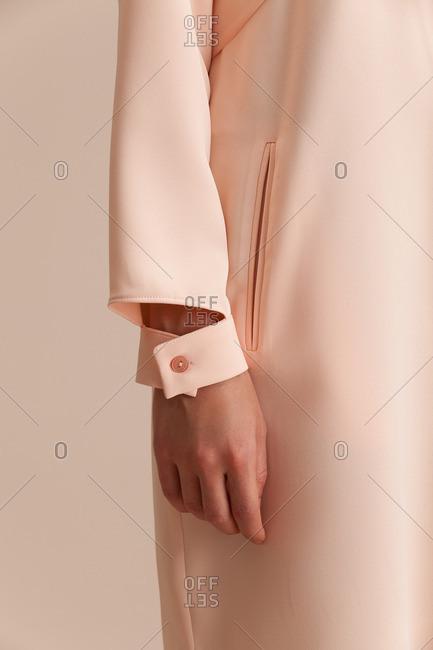 Arm of a woman wearing an elegant long-sleeve pink dress
