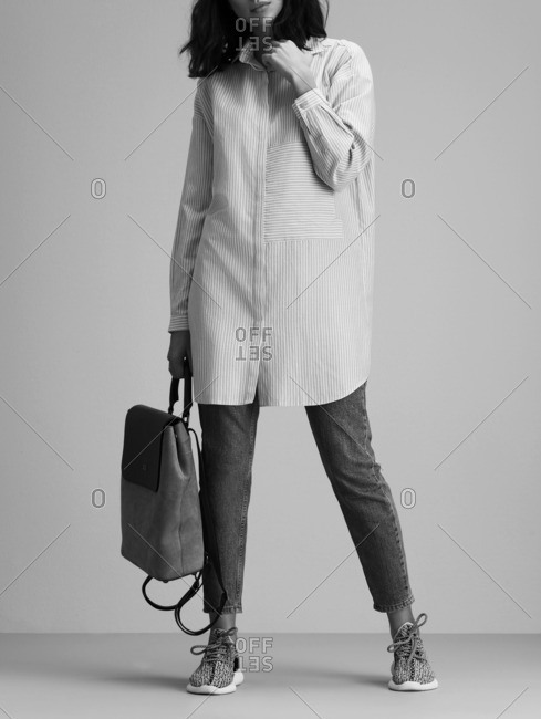 Woman wearing an oversized pinstripe shirt with a backpack