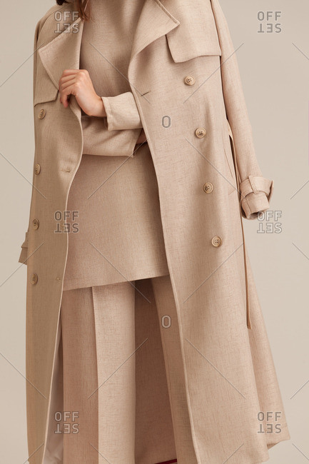 Woman in a neutral pantsuit and matching overcoat