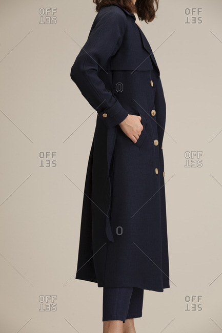Woman in a navy overcoat and cropped ankle pants