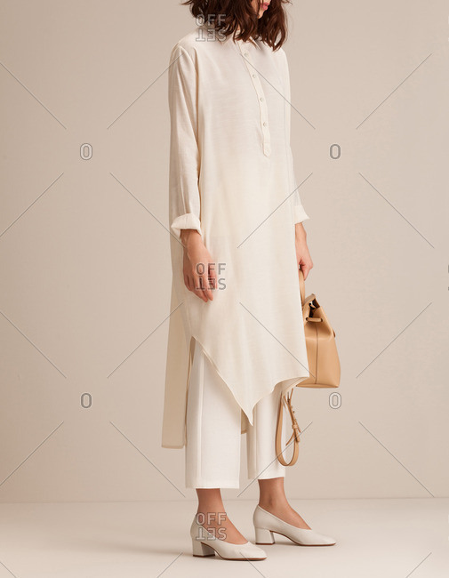 Woman in a long neutral tunic and chunky heeled shoes holding a bag