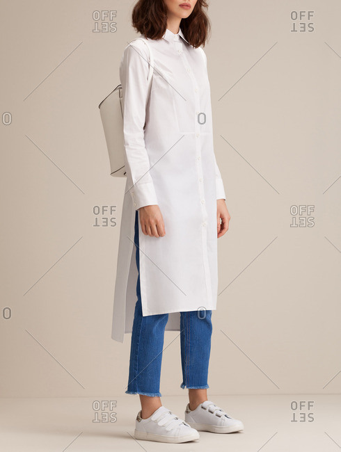 Woman in a long white tunic and ankle denim pants