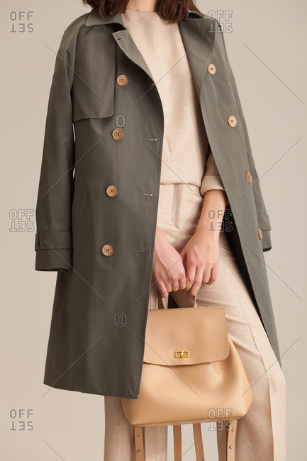 Woman in a neutral pantsuit with a green overcoat and purse