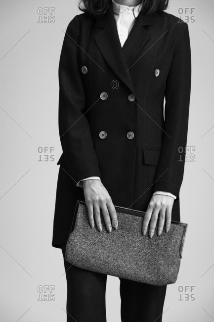 Woman in a peacoat holding a clutch purse