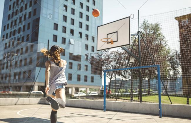 Young woman aiming at basketball hoop
