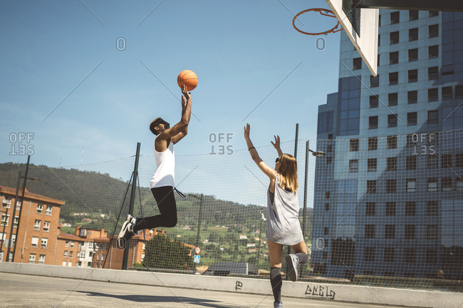Young couple playing basketball on court
