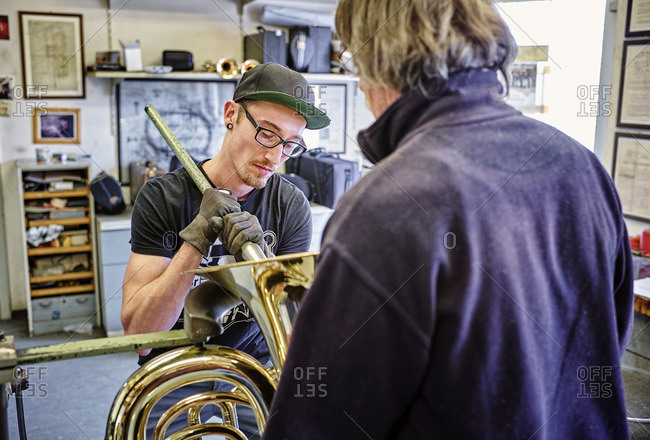 Two instrument makers repairing brass instrument in workshop