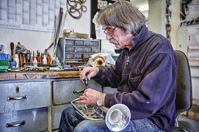 Instrument maker repairing trumpet in workshop