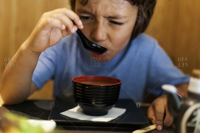 Little boy sitting in an Asian restaurant eating hot miso soup
