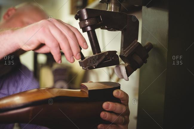 Close-up of a cobbler using a machine on a shoe sole in a workshop