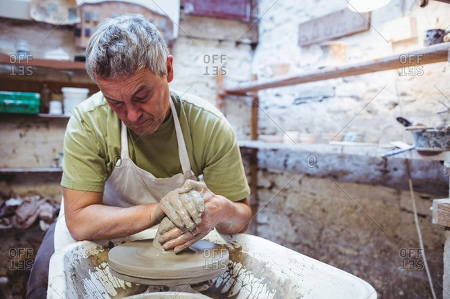 Craftsman making container while sitting in potter workshop