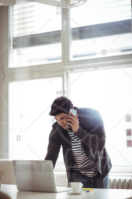 Photo editor talking on mobile phone while using laptop in creative office