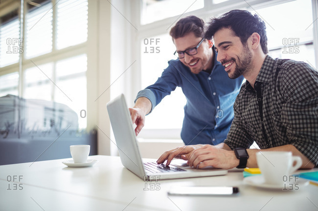 Photo editor showing something to happy coworker on laptop at creative office