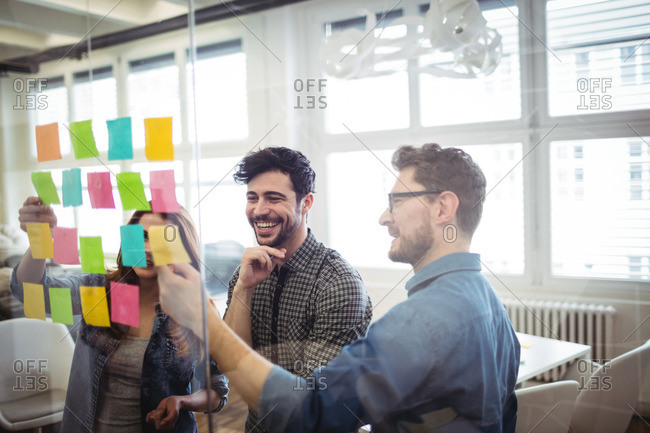 Cheerful creative business people looking at sticking notes on glass in office
