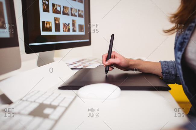 Midsection of photo editor using graphics tablet at creative office