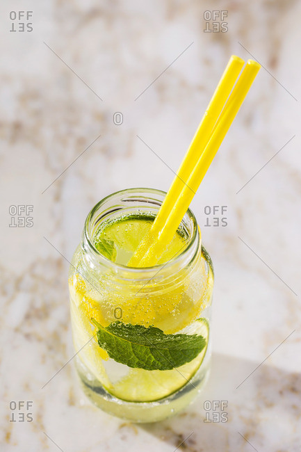 Sparkling water with mint and lemon slices on marble background