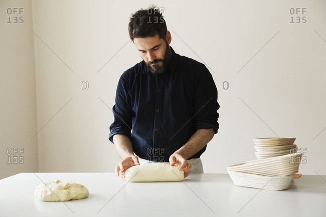 Baker standing at a table, shaping bread dough, a stack of rattan proofing baskets