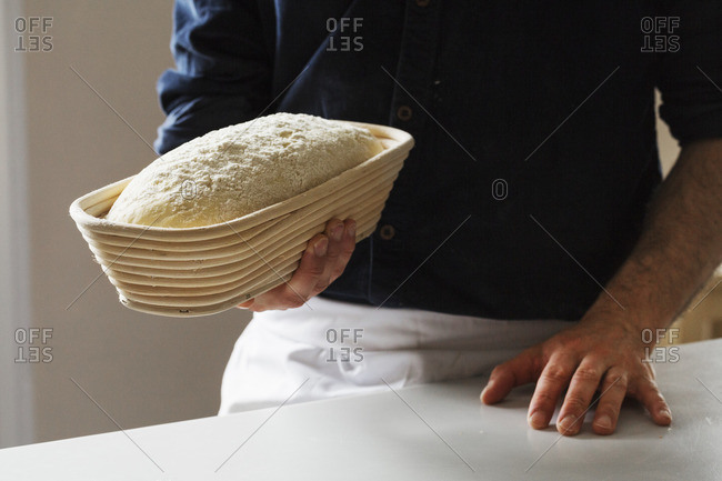 Close up of a baker holding a freshly baked loaf of white bread in a rattan proofing basket