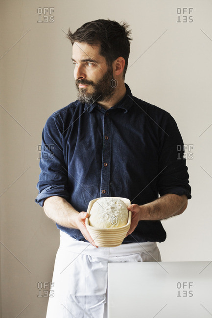 Baker holding a freshly baked loaf of white bread in a rattan proofing basket