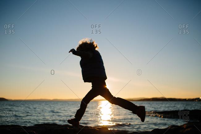 Boy jumping across rocks near the ocean
