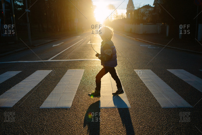 Little boy walking across a crosswalk at sunset