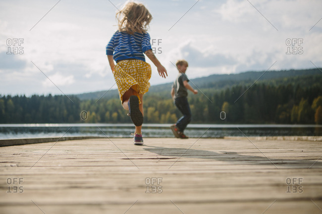 Brother and sister playing together on a lakeside pier