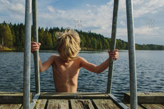 Boy climbing a ladder on a lakeside pier
