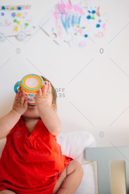 Toddler girl drinking from a sippy cup