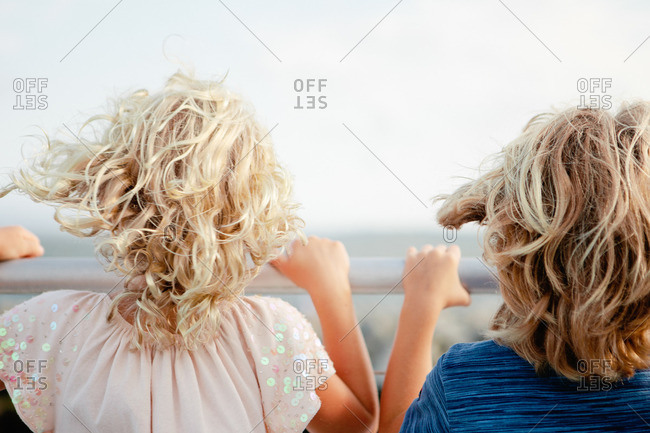 Blonde brother and sister standing at a railing