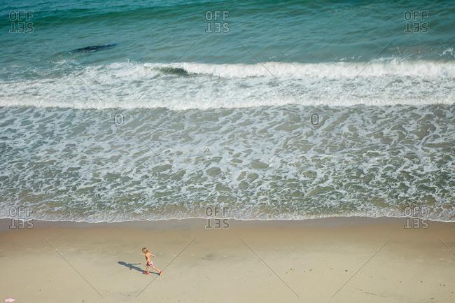 Little boy running across the sand at a seashore