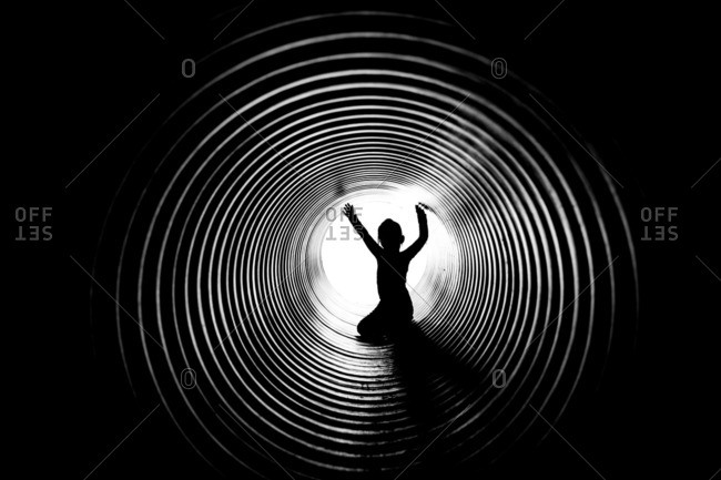 Girl silhouetted in drainage pipe