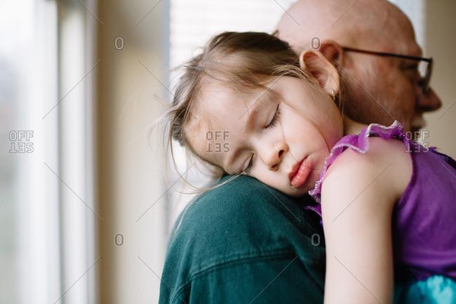 Girl asleep on older man's shoulder