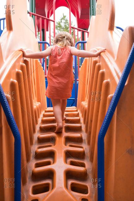 Girl climbing on playground play set