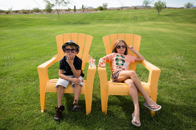 Children relaxing on yellow chairs drinking icy drinks