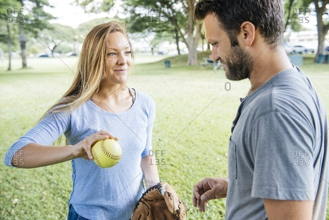 Woman holding softball by man