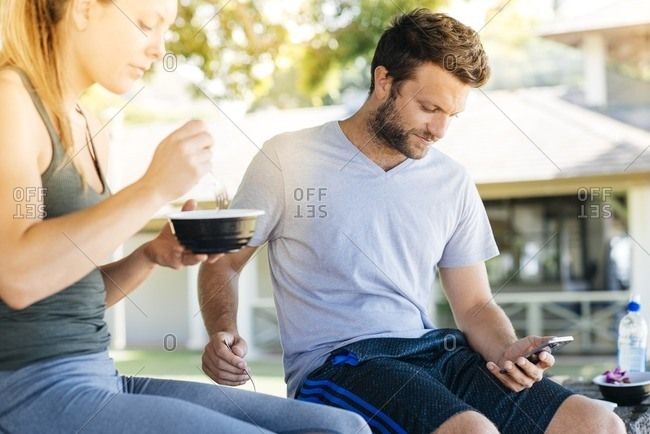 Woman eating as man checks phone