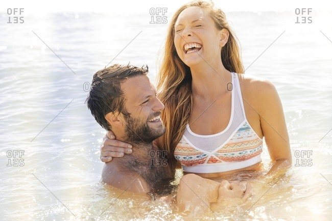Laughing couple in ocean water