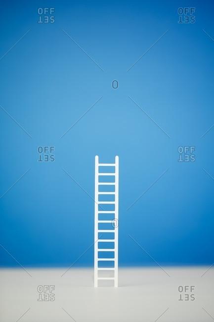Upright ladder on blue background