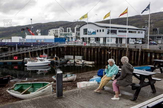 Scotland - August 31, 2015: Two older ladies drinking coffee on a picnic table by a harbor in the Scottish Highlands