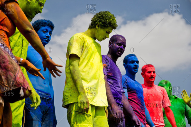 Cairo, Egypt - October 15, 2011: Men covered in bright colored powder at a color festival standing in a row