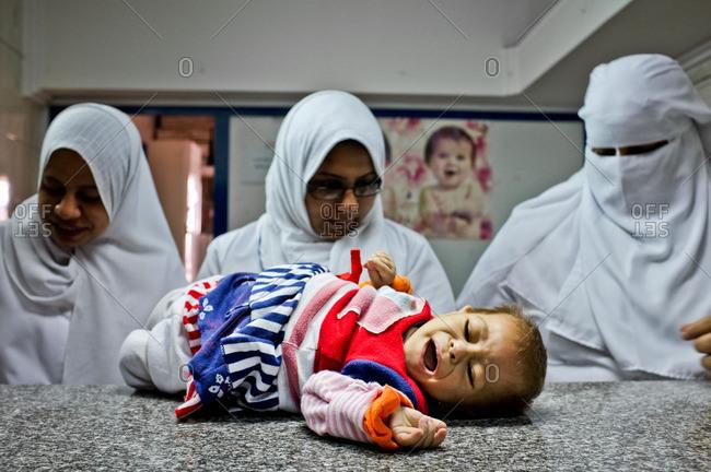 April 28, 2013: Three Muslim nurses examining baby